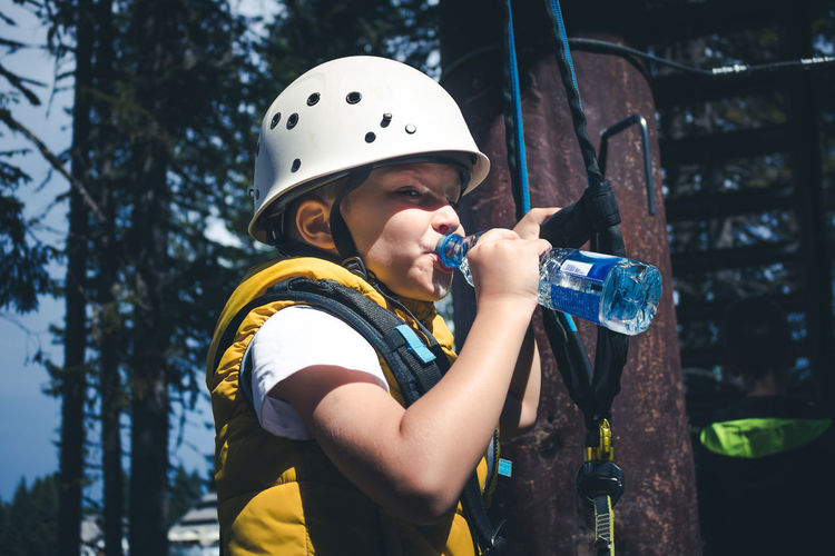 Small boy drinking water while taking a break on treetop during canopy tour in nature.