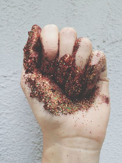 Cropped hand with glitters against wall