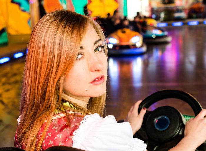 Portrait of woman sitting in bumper car at amusement park
