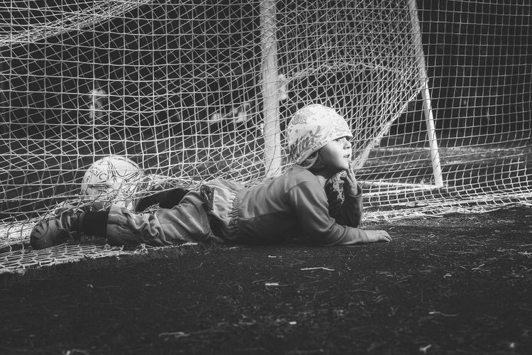 Playful Boy Lying On Playing Field In Soccer Goal