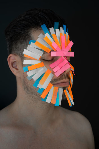 Close-up of shirtless man with adhesive notes on face against black background