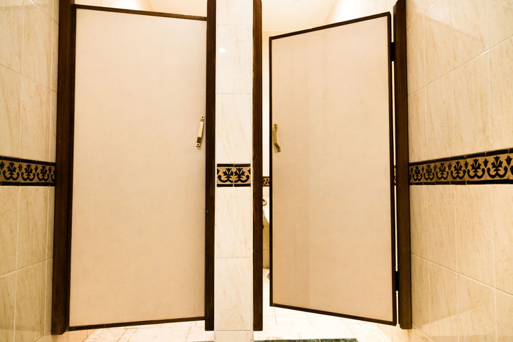 Public mens toilet cabins door in hotel. Low angle perspective, straight view, horizontal crop Low Angle View Toilet Architecture Bathroom Built Structure Cabin Call Close-up Closed Door Communication Day Door Exigency Finality Hotel Indoors  Inevitability Necessity Need No People Open Door Private Public Rest Room Urine