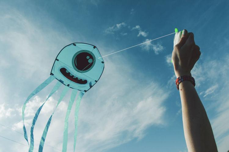 Cropped hand flying kite against sky
