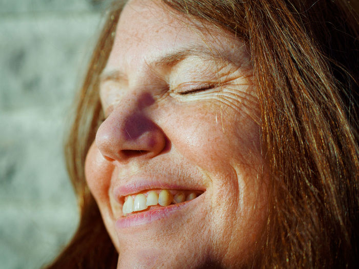Close-up of smiling woman with closed eyes at home