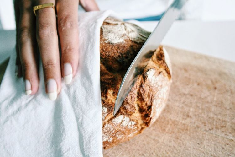 Cropped hand on woman cutting bread on cutting board