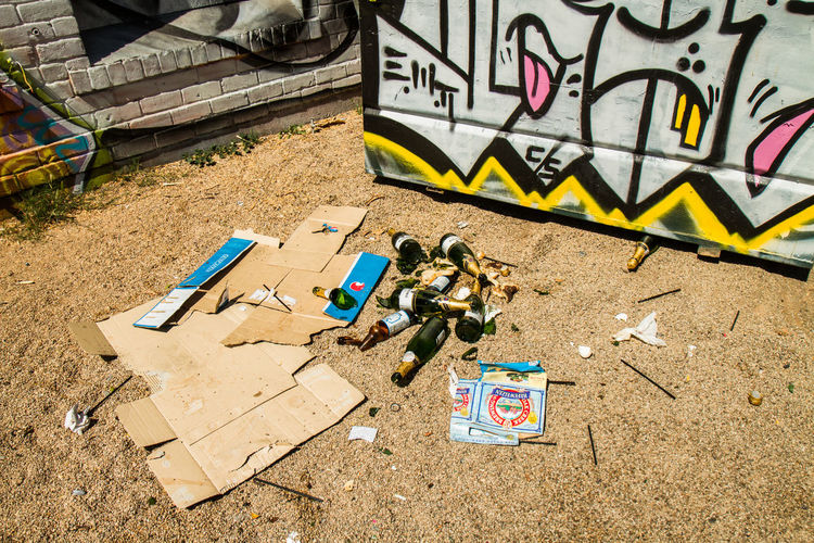 High angle view of broken liquor bottles by cardboard and graffiti