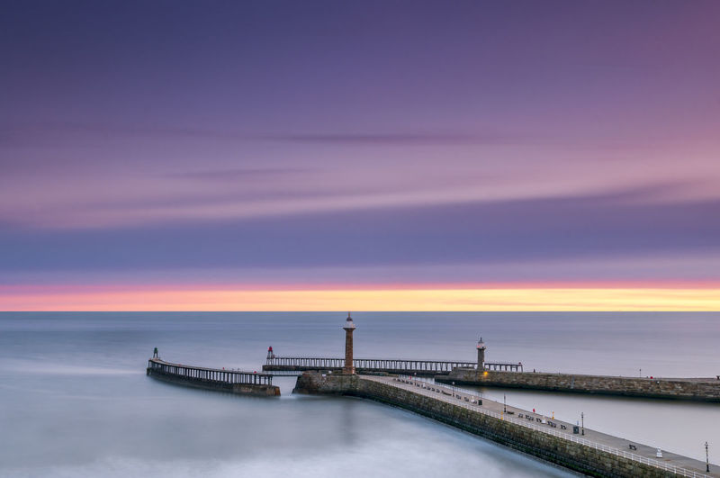 Lighthouses on pier over sea against cloudy sky during sunset