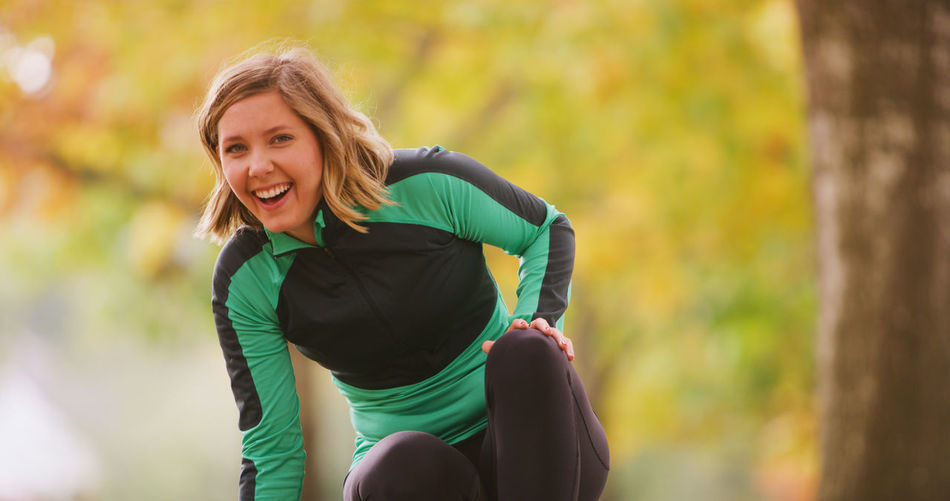 Portrait of cheerful young woman wearing sports clothing in park during autumn