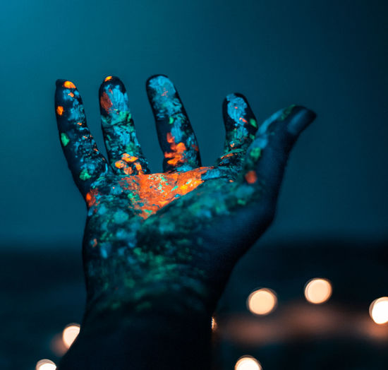 Close-up of painted hand against illuminated blue sky