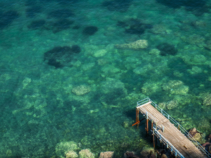 High angle view of pier by blue sea at sorrento on sunny day