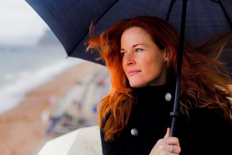Close-up of mature woman under umbrella