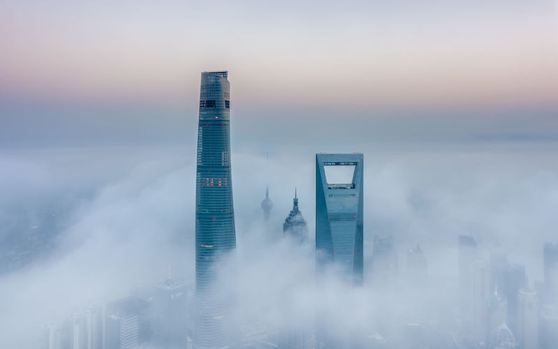 Shanghai tower and buildings against sky during foggy weather