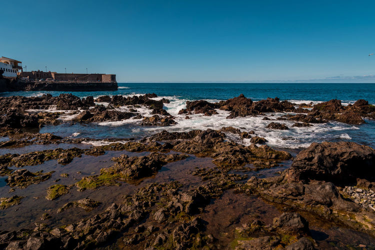 PUERTO DE LA CRUZ, TENERIFE / SPAIN - FEBRUARY 24 2018: View on bay of Puerto de la Cruz in the morning Architecture Beach Beauty In Nature Clear Sky Day Horizon Horizon Over Water Land Motion Nature No People Outdoors Pollution Rock Rock - Object Scenics - Nature Sea Sky Solid Water Wave