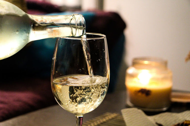 Cropped image of bottle pouring white wine in glass