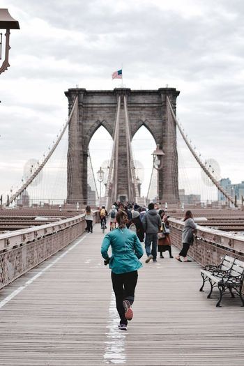 Rear view of woman jogging on brooklyn bridge