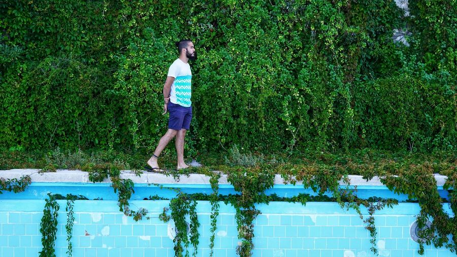 Full length of man standing by swimming pool