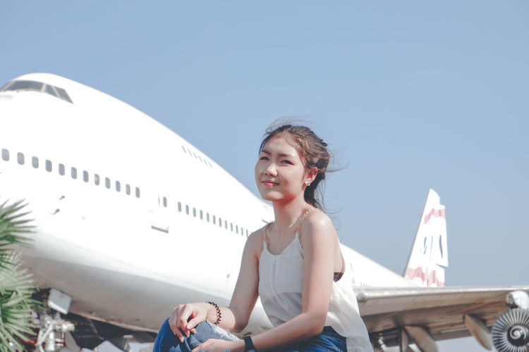 Smiling woman sitting against airplane