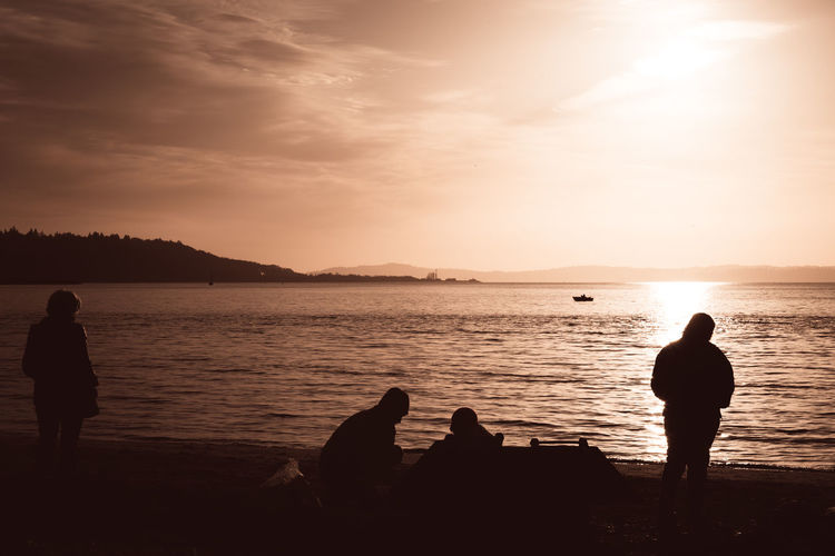 People relaxing and starting a campfire on the beach at Golden Gardens Park in Seattle. Ballard Beach Beauty In Nature Friendship Golden Gardens Park Horizon Over Water Leisure Activity Lifestyles Outdoors Real People Scenics Sea Seattle Shilshole Bay Silhouette Sky Sunset Togetherness Tranquility Travel Travel Destinations Traveling Vacations Water