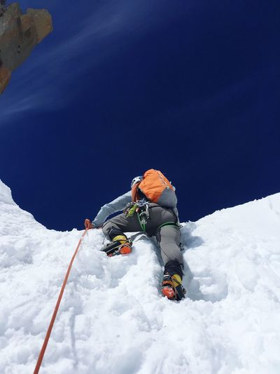 Low Angle View Of Person With Backpack Climbing Snowcapped Mountain Against Blue Sky