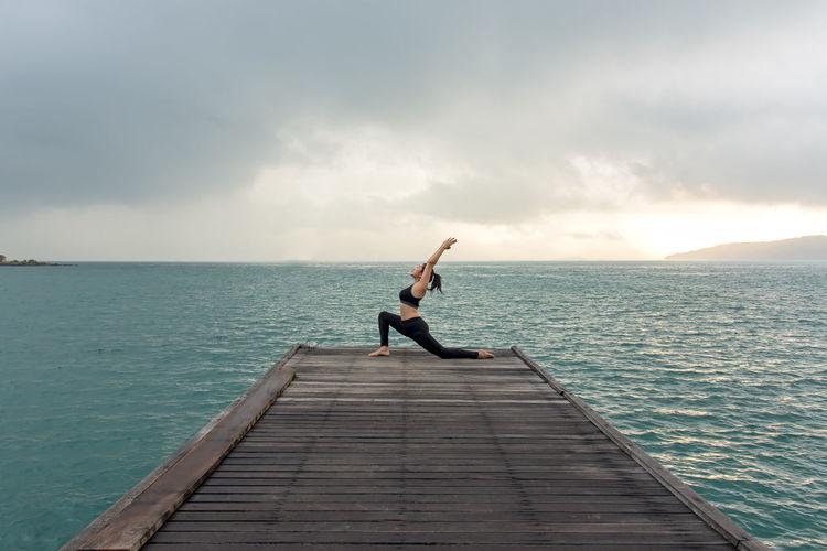 Man on pier over sea against sky
