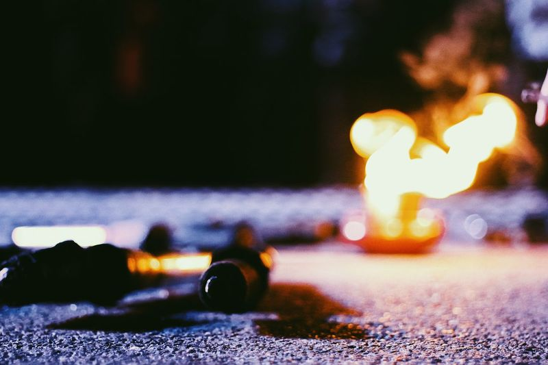 Close-up of lit candles on road at night