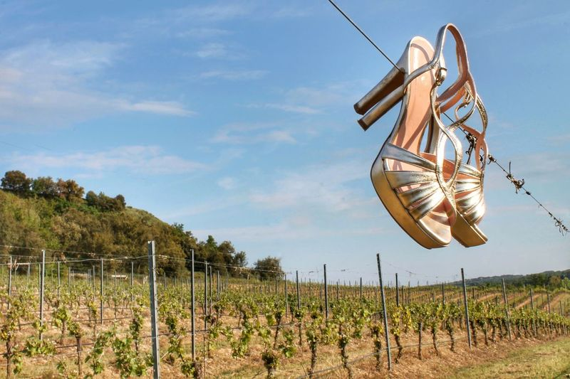 High heels hanging on cable against sky