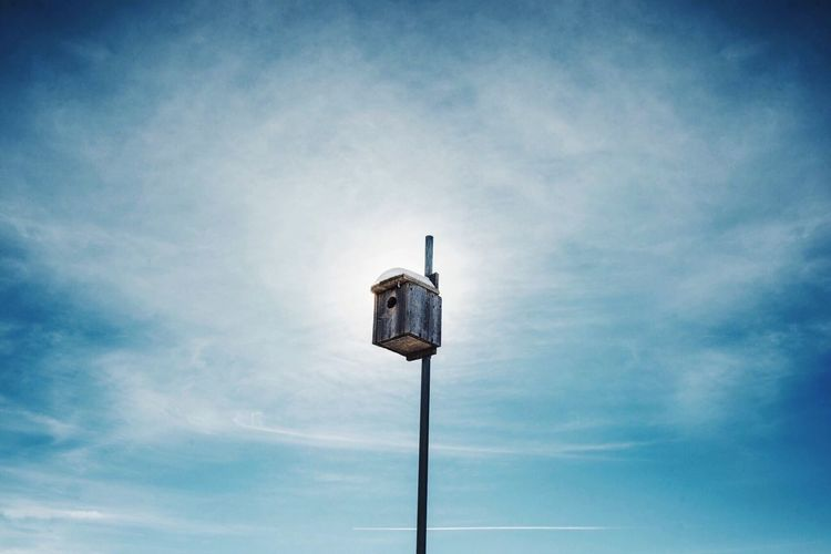 Low angle view of birdhouse on pole against blue sky