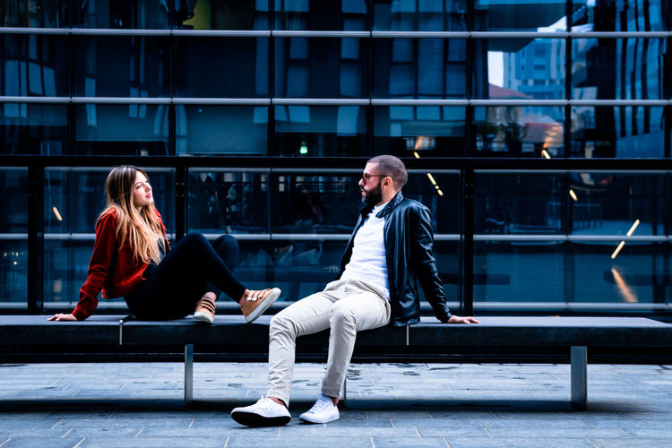 Couple sitting on bench in city