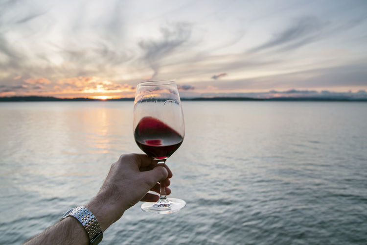 Point of view hand swirling red wine under a swirling cloud sunset over sea.