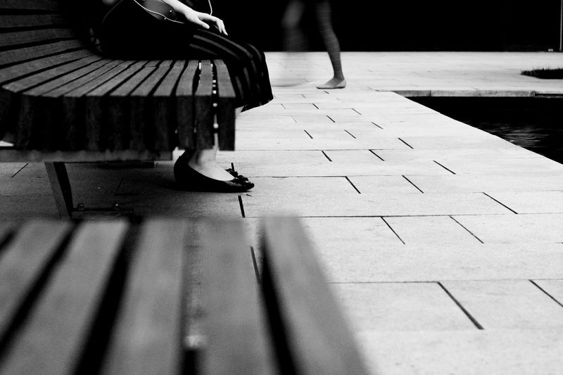 Low Section Of Woman Sitting On Bench