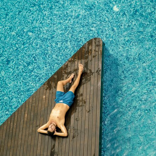 High Angle View Of Man Lying On Poolside