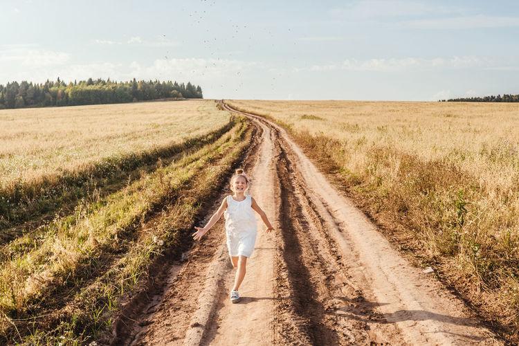 Full length of girl running on dirt road against sky