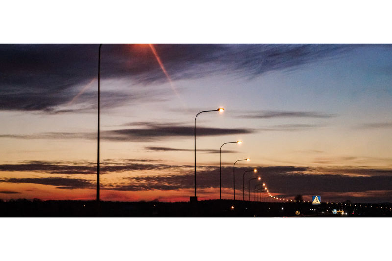 Road in city against sky during sunset