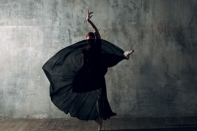 Woman dancing against gray wall