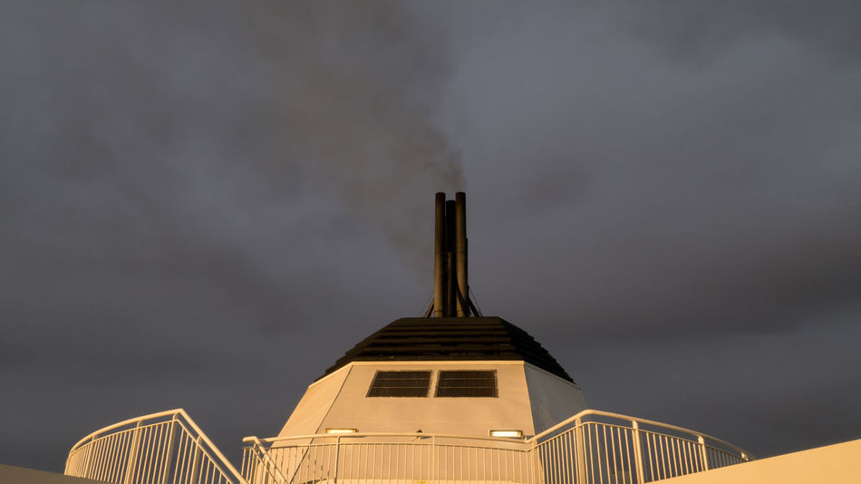 Close-up view of a chimney of a passanger ship with railing Black Burn Chimey Close-up Cloud Copy Space Dark Directly Below Energy Ferry Journey Nautical Vessel Passenger Ship Pollution Scary Sea Sky Smog Smoke Tourist Toxic Substance Transportation Travel Vacations Water