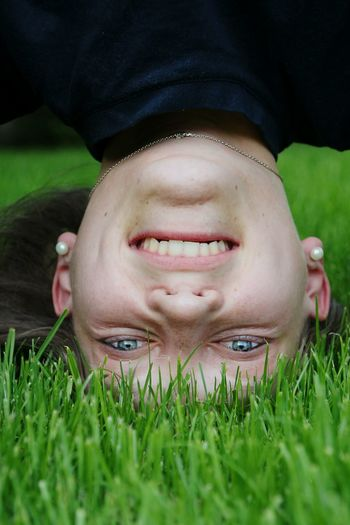 Portrait of smiling woman doing headstand on grass at park
