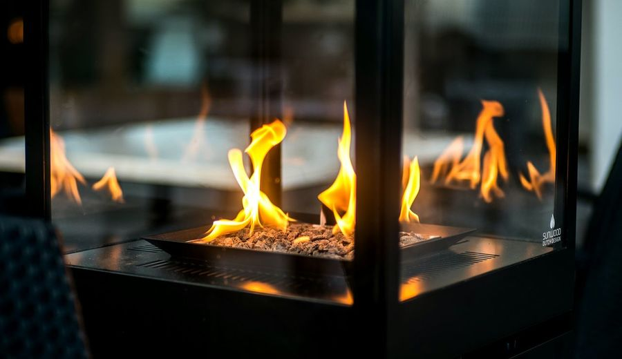 Close-up of burning candles on glass