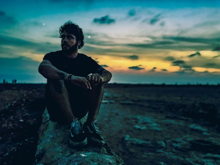Full length of young man sitting on land against sunset sky