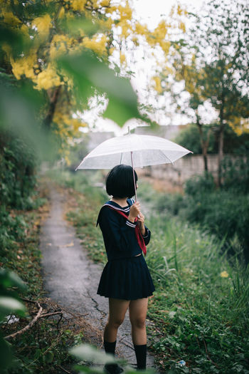 Full length of woman standing on footpath with umbrella during rainy season