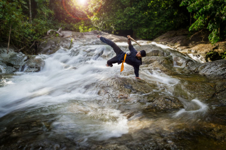 Man practicing handstand in river at forest