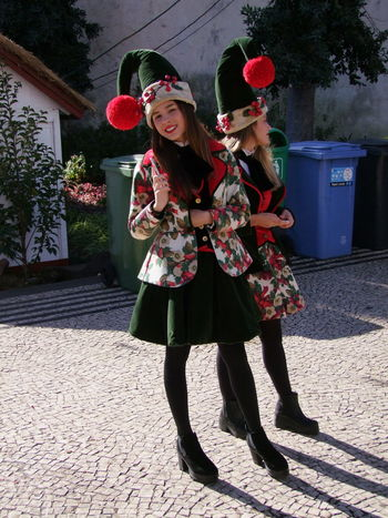 Two Young Women dressed as Christmas Elves, Avenida Arriaga Christmas City Composition Fun Funchal Madeira Madeira Island Portugal Standing Christmas Costumes Christmas Hats Front View Full Frame Full Length Happiness Looking At Camera Outdoor Photography Portrait Real People Smiling Standing Sunlight And Shadows Traditional Costumes Two Young Women Young Women