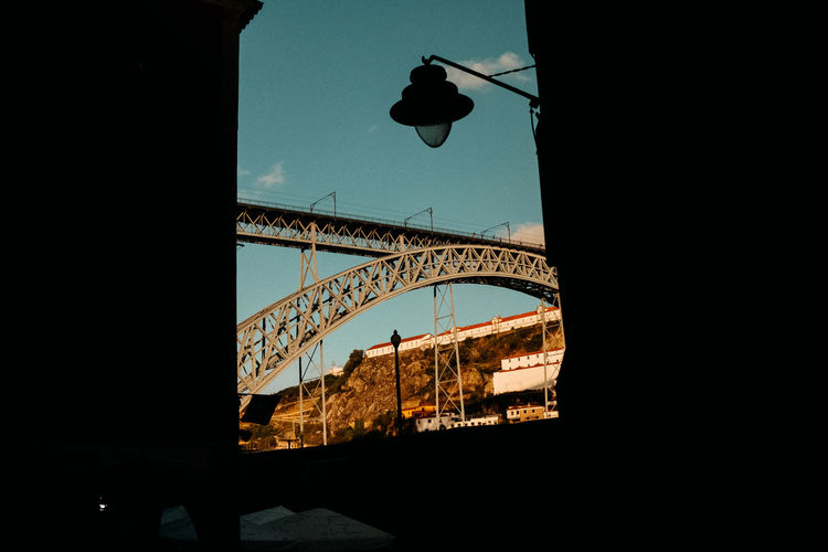 Low angle view of silhouette bridge against sky in city