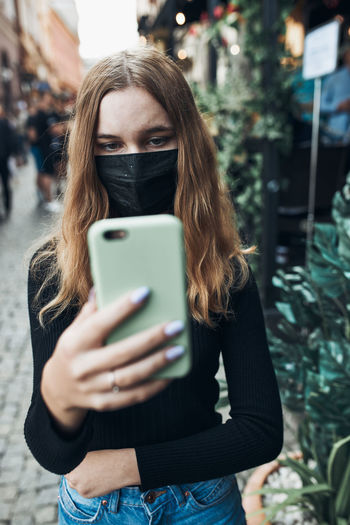 Girl wearing mask holding smart phone outdoors