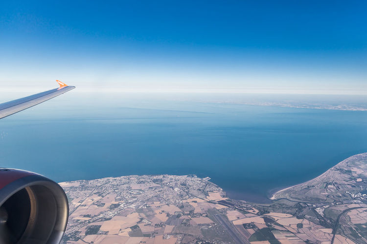 Airplane flying over manston international airport with sea and french coastline in background