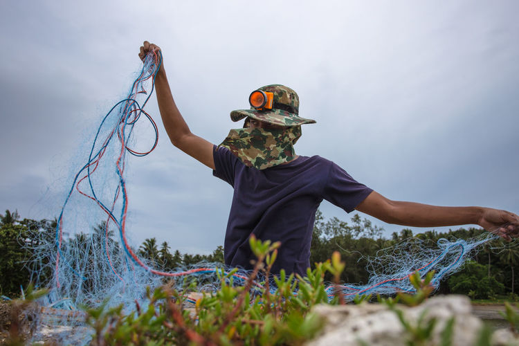 Fisherman holding fishing net on field against sky