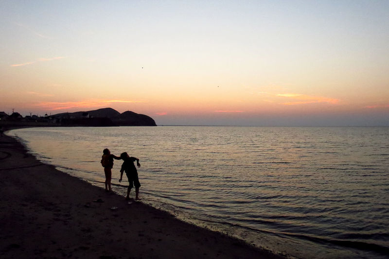 Beach Coastline Horizon Over Water Kids Playing Kids Playing At The Beach Ocean Outdoors Sand Scenics Sea Seascape Shore Sunset Throwing Rocks Tranquil Scene Vacations Water Îles De La Madeleine