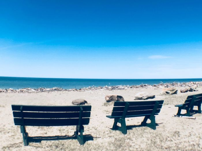 Bench at the breach EyeEm Selects Seat Sea Water Beach Sky Land Horizon Horizon Over Water Nature Blue Chair Sunlight Bench Beauty In Nature Tranquility Scenics - Nature Outdoors Copy Space Day Tranquil Scene