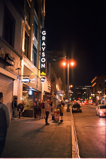 Group of people on city street at night