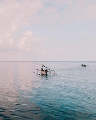 Fishing boat in sea against sky