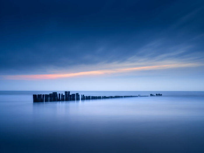 Breakwater along the beach of Schoorl during blue hour Sea Water Sky Horizon Over Water Horizon Scenics - Nature Blue Cloud - Sky Beauty In Nature Tranquil Scene Tranquility No People Nature Long Exposure Idyllic Waterfront Reflection Sunset Twilight Calm Dusk